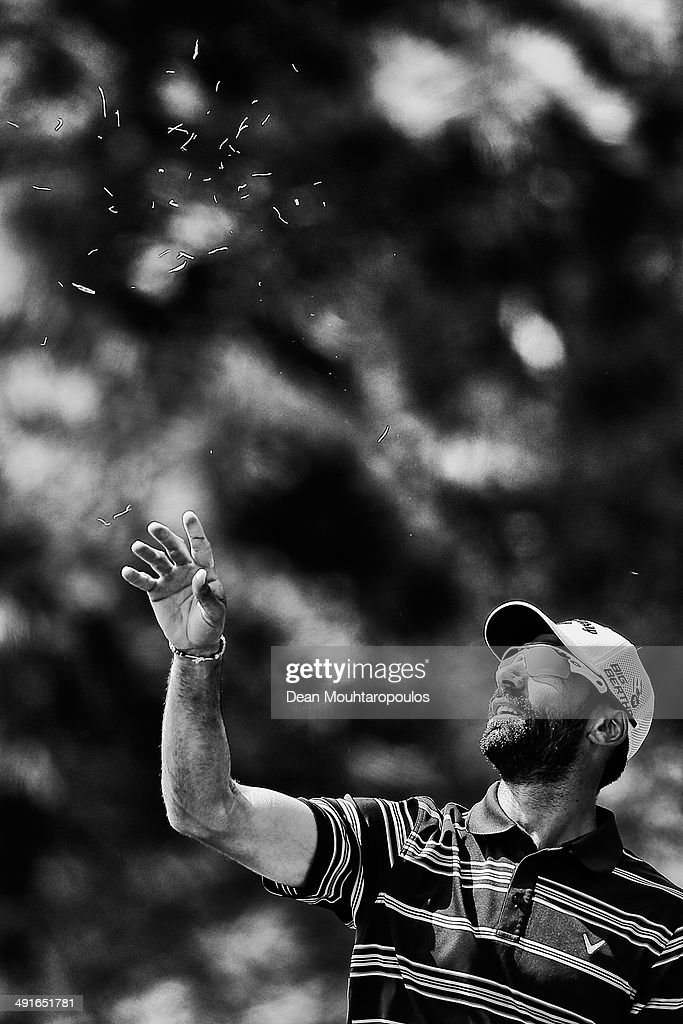Alvaro Quiros of Spain throws grass in the air to judge the wind direction before he hits his second shot on the 10th hole during Day 2 of the Open de Espana held at PGA Catalunya Resort on May 16, 2014 in Girona, Spain.