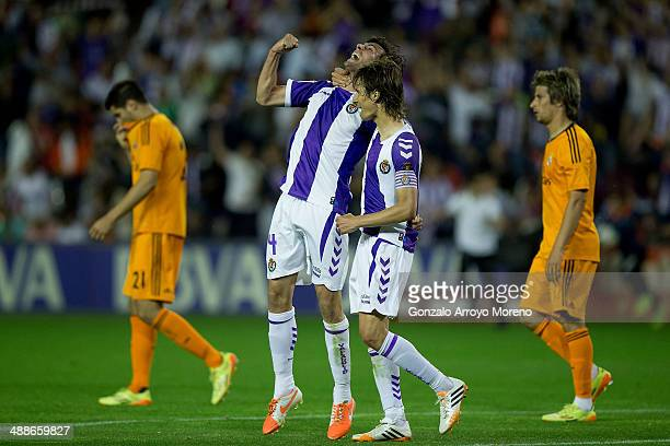 Alvaro Rubio of Real Valladolid CF celebrates their tie with his teammate Marc Valiente as Alvaro B Morata and Fabio Coentrao of Real Madrid CF leave...