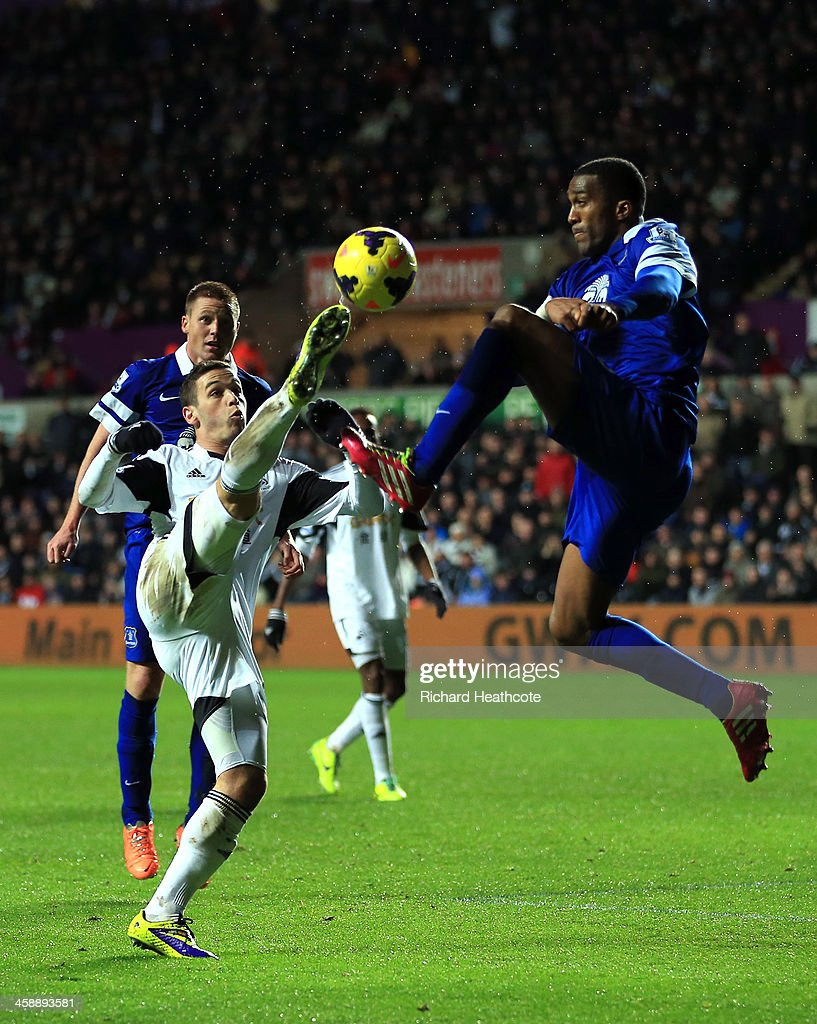 Alvaro Vazquez of Swansea and Sylvain Distin of Everton compete for the ball during the Barclays Premier League match between Swansea City and Everton at the Liberty Stadium on December 22, 2013 in Swansea, Wales.