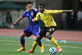 Alvas Powell of Jamaica and Yuto Nagatomo of Japan competes for the ball during the international friendly match between Japan and Jamaica at Denka...