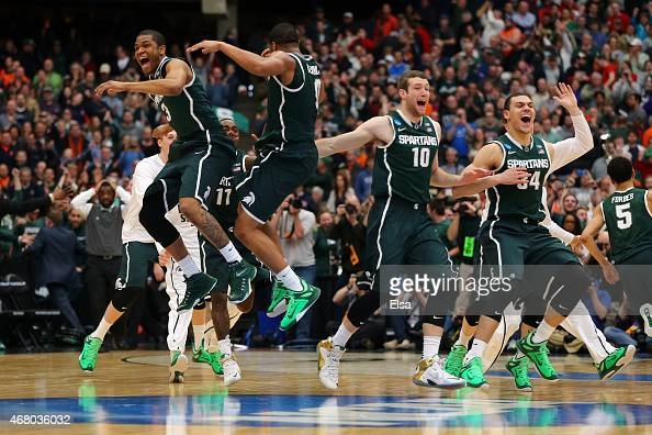 Alvin Ellis III and Marvin Clark Jr #0 of the Michigan State Spartans celebrate defeating the Louisville Cardinals 76 to 70 in overtime of the East...