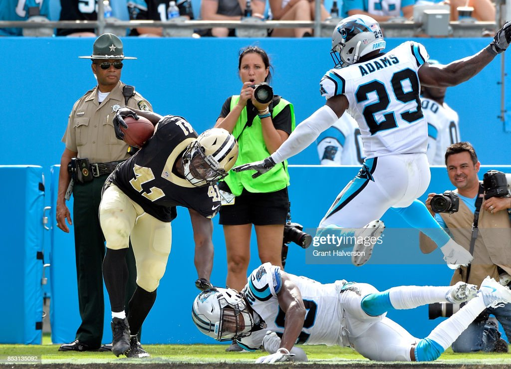 Alvin Kamara #41 of the New Orleans Saints beats Mike Adams #29 and Daryl Worley #26 of the Carolina Panthers to the3 end zone for a touchdown during their game at Bank of America Stadium on September 24, 2017 in Charlotte, North Carolina.