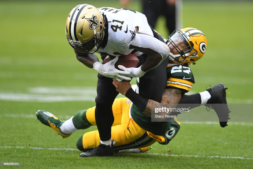 Alvin Kamara #41 of the New Orleans Saints is brought down by Josh Jones #27 of the Green Bay Packers during a game at Lambeau Field on October 22, 2017 in Green Bay, Wisconsin. The Saints defeated the Packers 26-17.