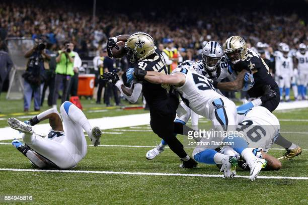 Alvin Kamara of the New Orleans Saints scores a touchdown as Luke Kuechly of the Carolina Panthers defends during the first half of a game at the...