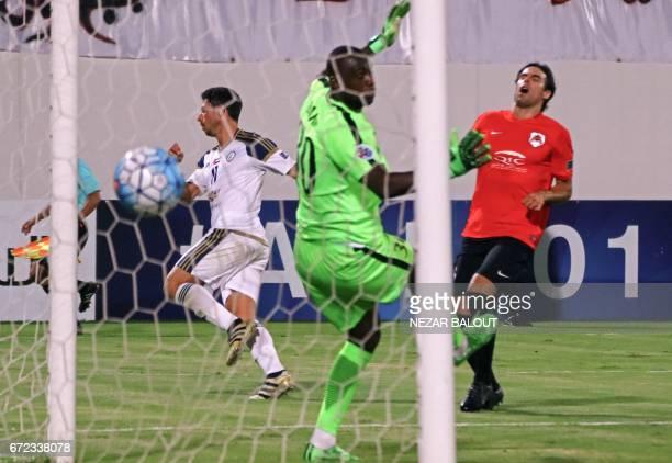 UAE AlWahda FC's Argentinian forward Sebastian Tagliabue scores a goal against Qatar's AlRayyan SC goalkeeper Omar Bari as his Uruguayan teammate...