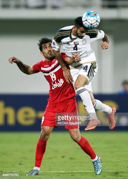 AlWahda's Salem Sultan heads the ball in front of Persepolis's Vahid Amiri during the AFC Champions League qualifying football match between UAE's...