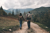 Full length rear view of young couple holding hands while hiking in mountains