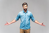 Studio shot of handsome young man in casual wear looking at camera and keeping hands outstretched
