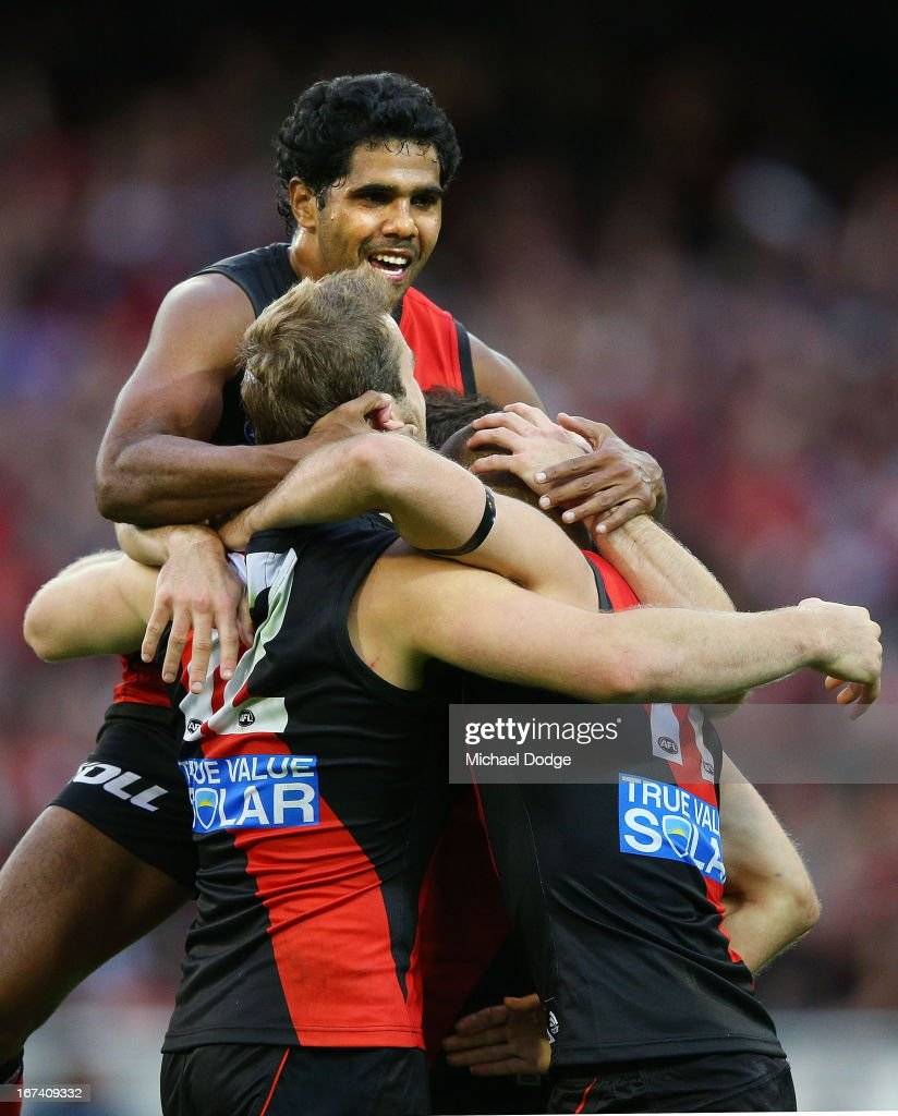 Alwyn Davey leaps on Stewart Crameri and David Zaharakis (R) of the Bombers after a goal during the round five AFL match between the Essendon Bombers and the Collingwood Magpies at Melbourne Cricket Ground on April 25, 2013 in Melbourne, Australia.