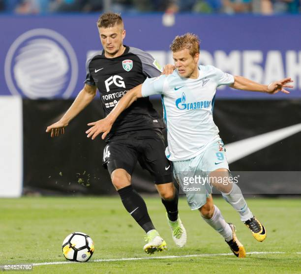 Alyaksandr Karnitsky of FC Tosno and Aleksandr Kokorin of FC Zenit Saint Petersburg vie for the ball during the Russian Football League match between...