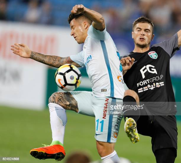 Alyaksandr Karnitsky of FC Tosno and Sebastian Driussi of FC Zenit Saint Petersburg vie for the ball during the Russian Football League match between...