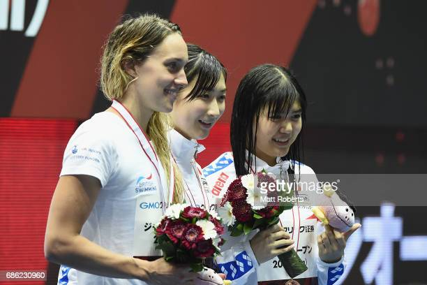 Alys Thomas of Great Britain Rikako Ikee of Japan and Suzuka Hasegawa of Japan pose with their medals on the podium after the 100m Butterfly Final...