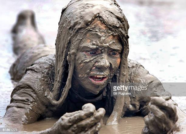 Alyssa Braun age 12 of Canton Michigan examines her hands while lying in a giant lake of mud at the annual Mud Day celebration July 8 2008 in...