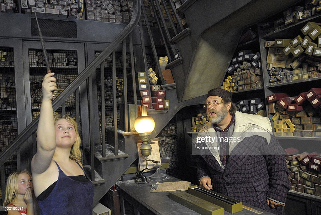 Alyssa Middleton, 14, left, of Granite Bay, California, U.S., waves a wand at the instruction of an actor portraying the wandkeeper inside Ollivanders at the Universal Studios Wizarding World of Harry Potter theme park in Orlando, Florida, U.S., on Thursday, June 17, 2010. Universal reportedly spent $265 million building the theme park, based on a Securities & Exchange Commission filing. Photographer: Phelan M. Ebenhack/Bloomberg via Getty Images