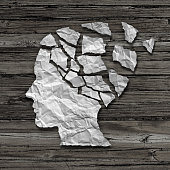 Alzheimer patient medical mental health care concept as a sheet of torn crumpled white paper shaped as a side profile of a human face on an old grungy wood background as a symbol for neurology and dem