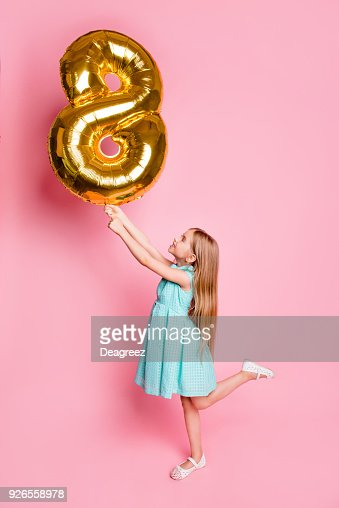 I am 8 years old! Vertical full-length side profile view portrait of cute lovely beautiful girl celebrating birthday, she is holding golden balloon in shape of figure-eight isolated on pink background : Stock Photo