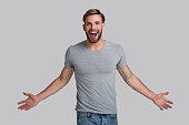 Charming young man keeping arms outstretched and shouting while standing against grey background