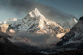 Ama Dablam mountain at sunset and blue sky. Sun illuminates slopes. Himalayan mountains, Nepal.