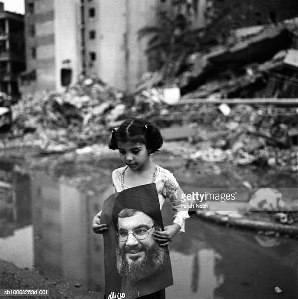 Amal carries a poster of Hezbollah leader Hassan Nasrallah among the rubble on August 31 2006 in Dahiya the southern suburb district of Beirut The...