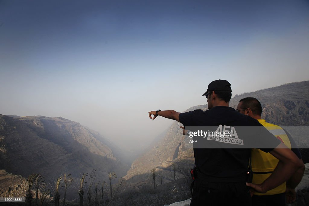 Aman points to a smoke covered valley in Valle Gran Rey on August 13, 2012, on the Spanish canary island of La Gomera. Wildfires killed two people in south-eastern-Spain and forced thousands to evacuate in the Canary Islands where flames ravaged a rare nature reserve, authorities said Monday.