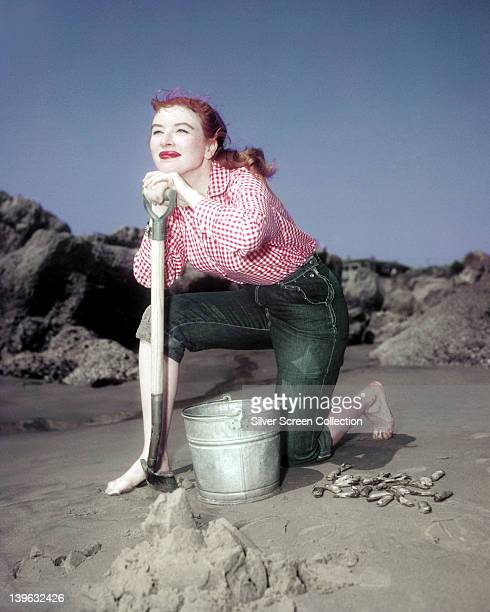 Amanda Blake US actress wearing a red and white check shirt posing with a shovel and bucket kneeling on sand in a publicity portrait issued for the...