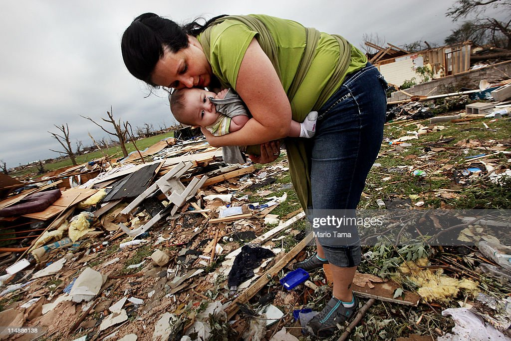 Amanda Carper holds her son Silas, 5 months, as she searches through the rubble of her deceased grandfather Charles Oster's home after a massive tornado passed through the town killing at least 132 people on May 27, 2011 in Joplin, Missouri. Oster was 77 years old and perished during the tornado. The town continues the process of recovering from the storm which damaged or destroyed an estimated 8,000 structures.