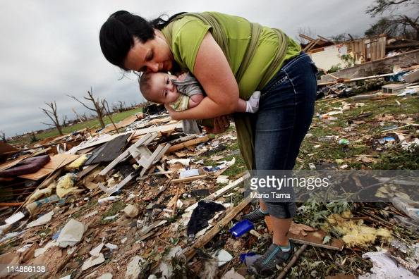 Amanda Carper holds her son Silas 5 months as she searches through the rubble of her deceased grandfather Charles Oster's home after a massive...