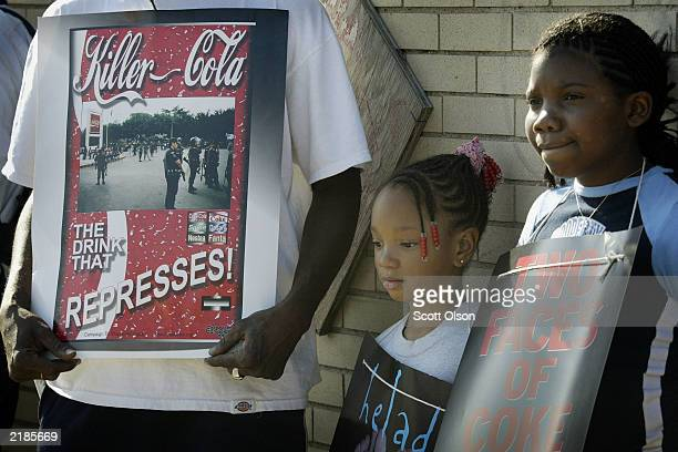 Amanda Johnson and her sister Melinique demonstrate with their father in front of a CocaCola distribution center July 22 2003 in Chicago Illinois...