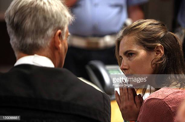 Amanda Knox chats with her lawyer Carlo Della Vedova as she attends a session of her appeal against her murder conviction in Perugia's Court of...