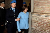 Amanda Knox is led into Perugia's court of Appeal by a police officer for the first session of her appeal against her murder conviction on November...
