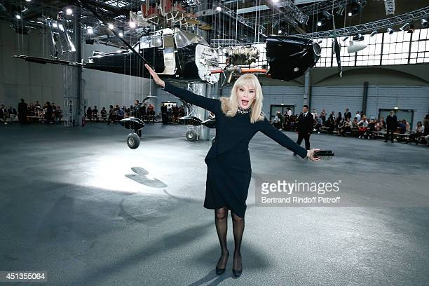 Amanda Lear posing front of Holland Paul Veroude's work attends the Givenchy show as part of the Paris Fashion Week Menswear Spring/Summer 2015 on...