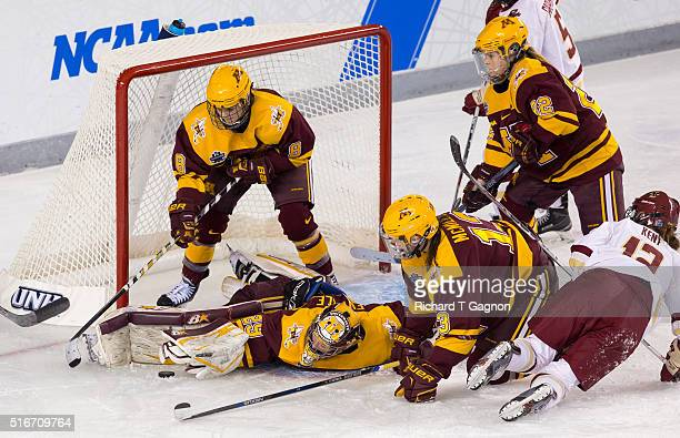 Amanda Leveille of the Minnesota Golden Gophers makes a blocker glove save against Makenna Newkirk of the Boston College Eagles as teammates Milica...