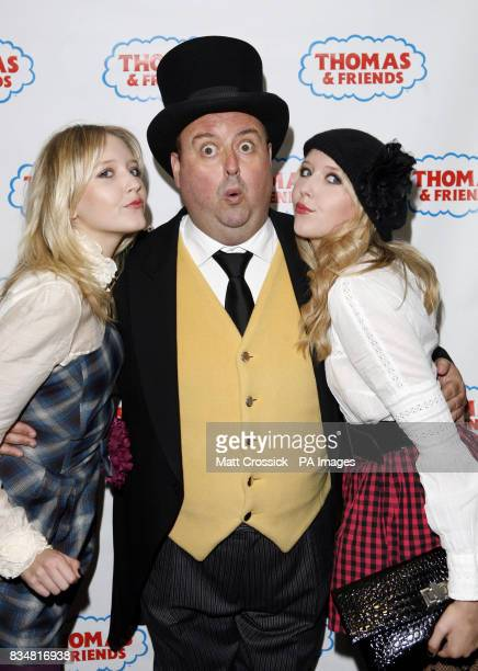 Amanda Marchant and Samantha Marchant pose with a man dressed in costume as the character of the Fat Controller from the Thomas the Tank Engine...