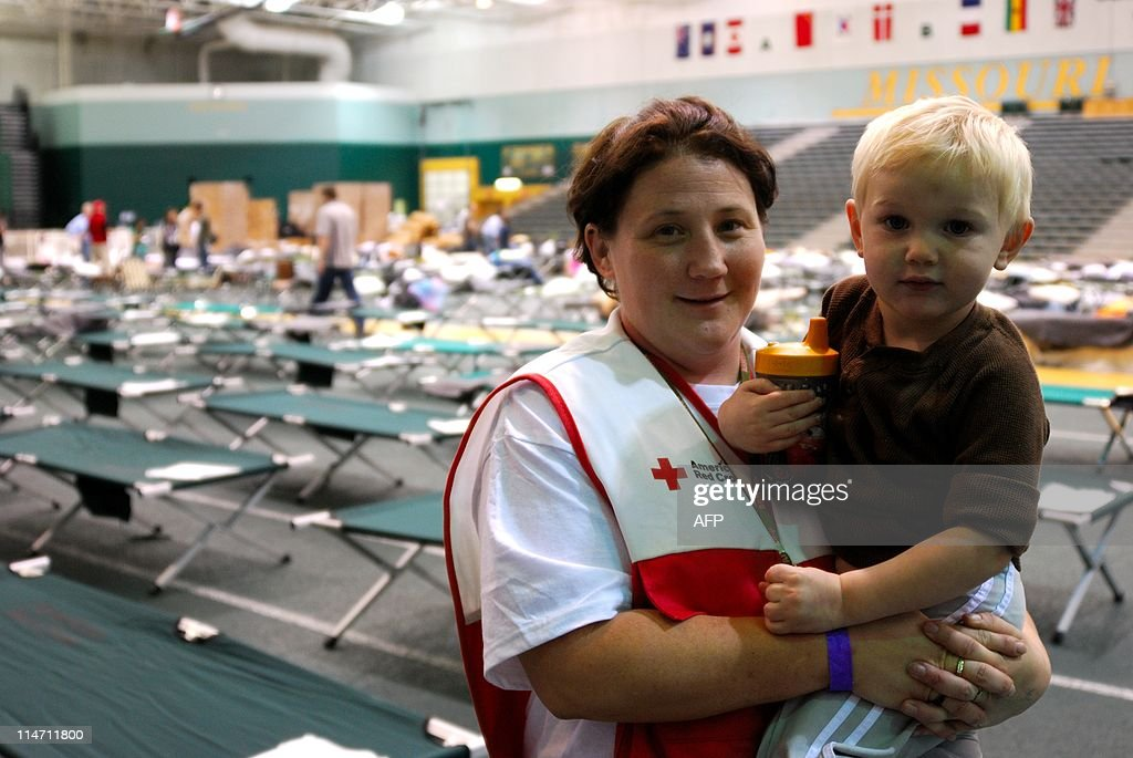 Amanda Marshall, assistant shelter manager for the Red Cross, takes a break with her son Joe on May 25, 2011, three days after a massive tornado tore through Joplin, Missouri leaving 125 dead and 1,500 reported missing. Marshall keeps checking her cell phone, waiting for news about her missing four-year-old niece. AFP PHOTO / Mira OBERMAN
