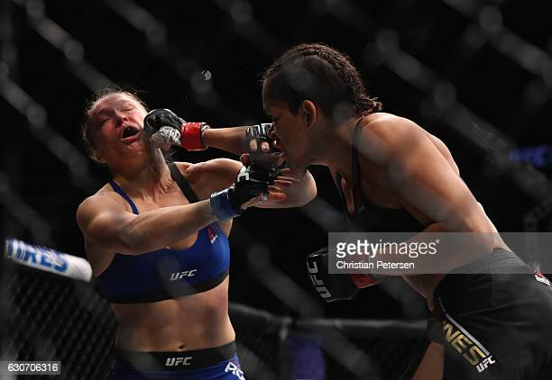 Amanda Nunes of Brazil punches Ronda Rousey in their UFC women's bantamweight championship bout during the UFC 207 event on December 30 2016 in Las...