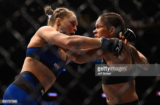 Amanda Nunes of Brazil punches Ronda Rousey in their UFC women's bantamweight championship bout during the UFC 207 event at TMobile Arena on December...
