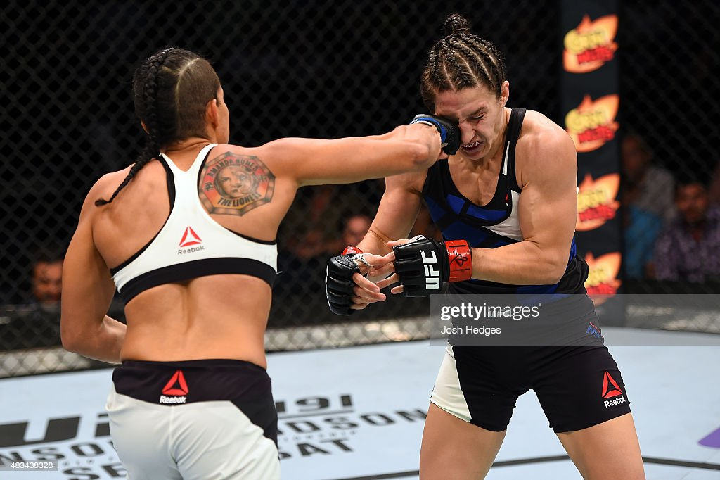 Amanda Nunes of Brazil punches Sara McMann in their women's bantamweight bout during the UFC Fight Night event at Bridgestone Arena on August 8, 2015 in Nashville, Tennessee.