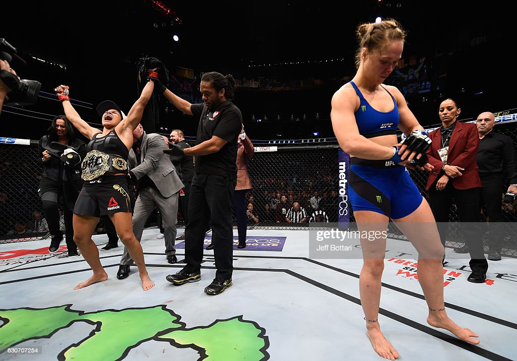 Amanda Nunes of Brazil (left) reacts to her victory over Ronda Rousey (right) in their UFC women's bantamweight championship bout during the UFC 207 event at T-Mobile Arena on December 30, 2016 in Las Vegas, Nevada.