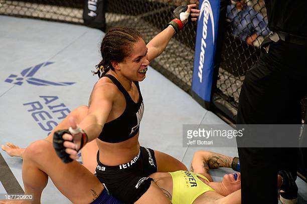 Amanda Nunez celebrates after defeating Germaine de Randamie in their UFC women's bantamweight bout on November 6 2013 in Fort Campbell Kentucky