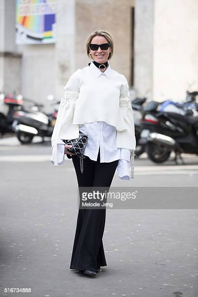 Amanda Shadforth of Oracle Fox blog wears an cream Ellery cropped blouse with ties around the arms a neck accessory a white shirt and black...
