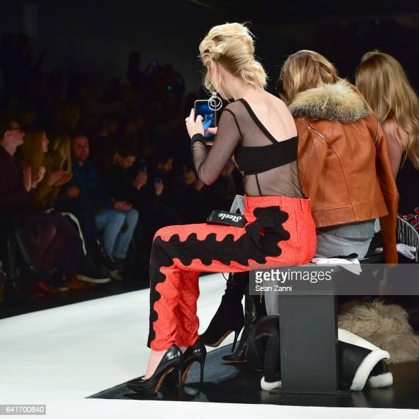 Amanda Steele takes a photo of models on the runway at the Jonathan Simkhai show during New York Fashion Week at Skylight Clarkson Sq on February 11...