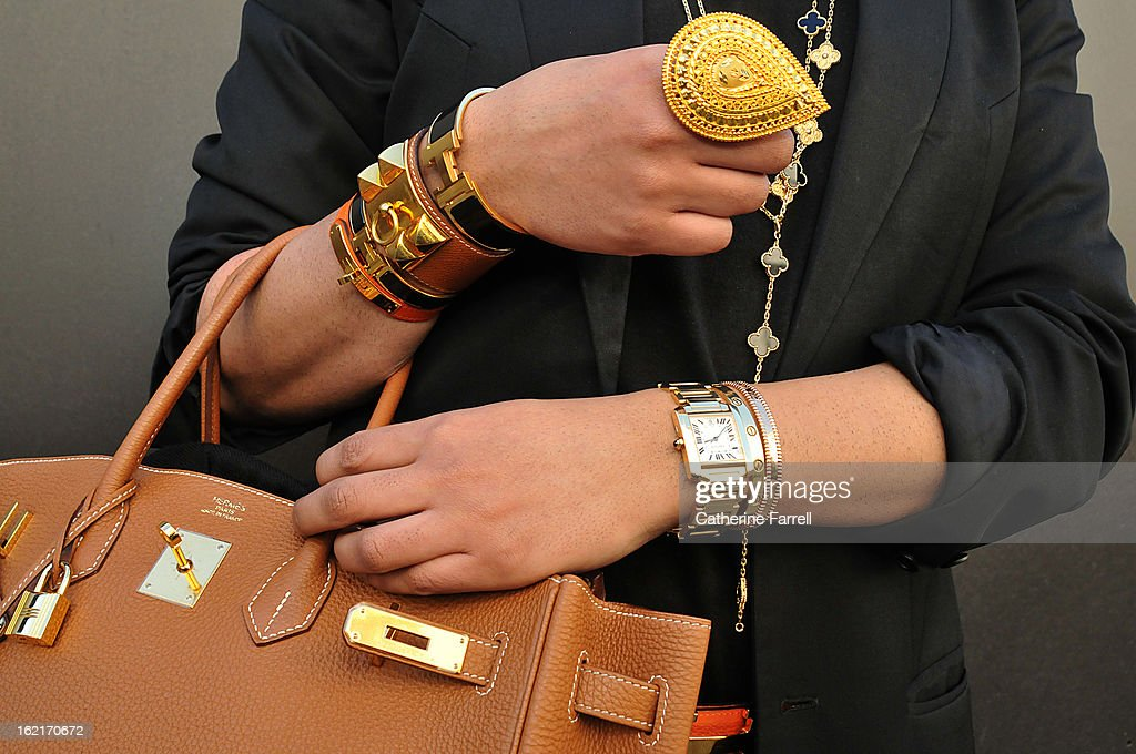Amar Hussain Pakastani stylist wearing an Alexandrer Mc Queen First Collection coat,accessorised with Michael Kors sunglasses,Van Cleef and Arepels neck chains and earring, Cartier and Van Cleef bangles, Cartier watch,Hermes cuffs, Hermes belt and bag,at London Fashion Week Fall/Winter 2013/14 on February 19, 2013 in London, England.