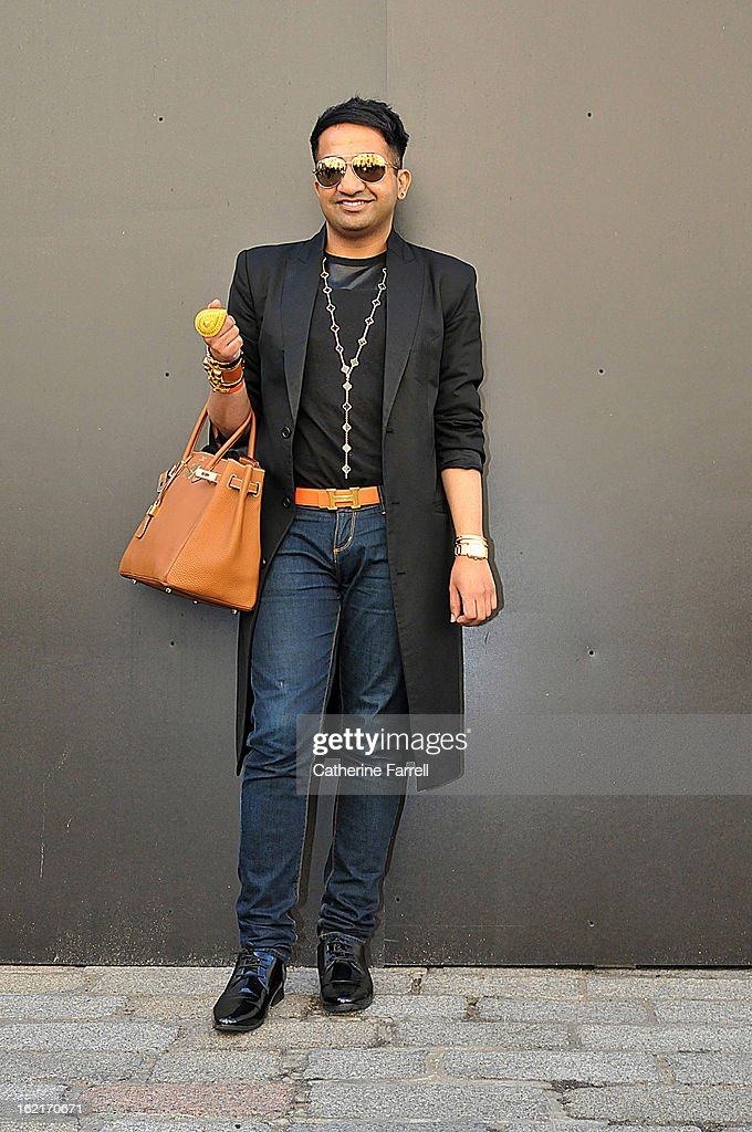 Amar Hussain Pakastani stylist wears an Alexander McQueen first collection coat, skinny jeans from the High Street, accessorised with Michael Kors sunglasses, Van Cleef and Arpel earring and neck chains, cuffs from Hermes, Cartier and Van Cleef and Arpels, pear shape Indian outsized gold ring, and vintage shoes at London Fashion Week Fall/Winter 2013/14 on February 19, 2013 in London, England.