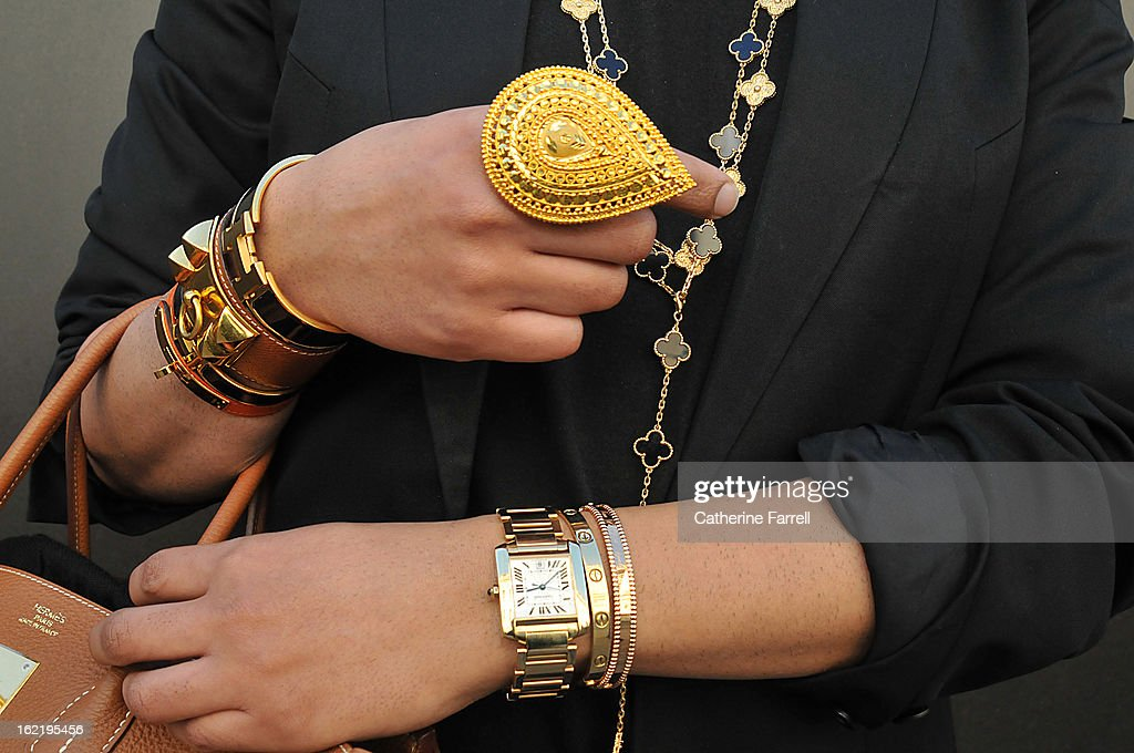 Amar Hussain, Pakastani stylist wears an Alexandrer Mc Queen First Collection coat, with skinny jeans from the High Street accessorised with Van Cleef and Arepels neck chains and earring, Cartier and Van Cleef bangles, Indian outsized pear shaped gold ring, Cartier watch,Hermes cuffs, Hermes belt and bag, at London Fashion Week Fall/Winter 2013/14 on February 19, 2013 in London, England.