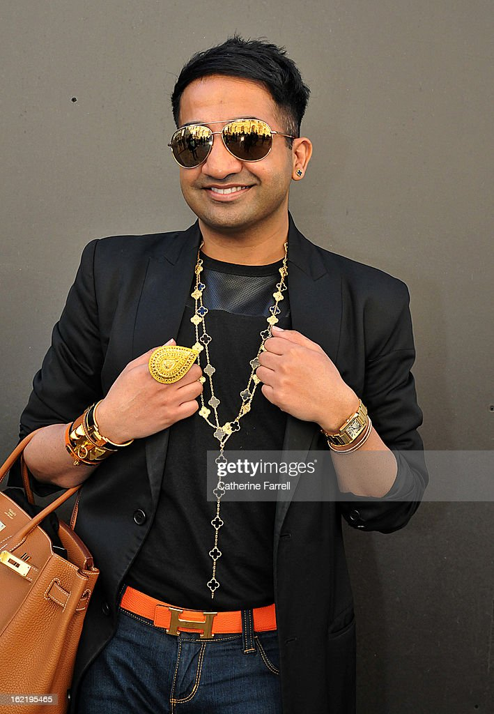 Amar Hussain, Pakastani stylist wears an Alexandrer Mc Queen First Collection coat, with skinny jeans from the High Street accessorised with Michael Kors sunglasses,Van Cleef and Arepels neck chains and earring, Cartier and Van Cleef bangles, Indian outsized pear shaped gold ring, Cartier watch,Hermes cuffs, Hermes belt and bag, at London Fashion Week Fall/Winter 2013/14 on February 19, 2013 in London, England.