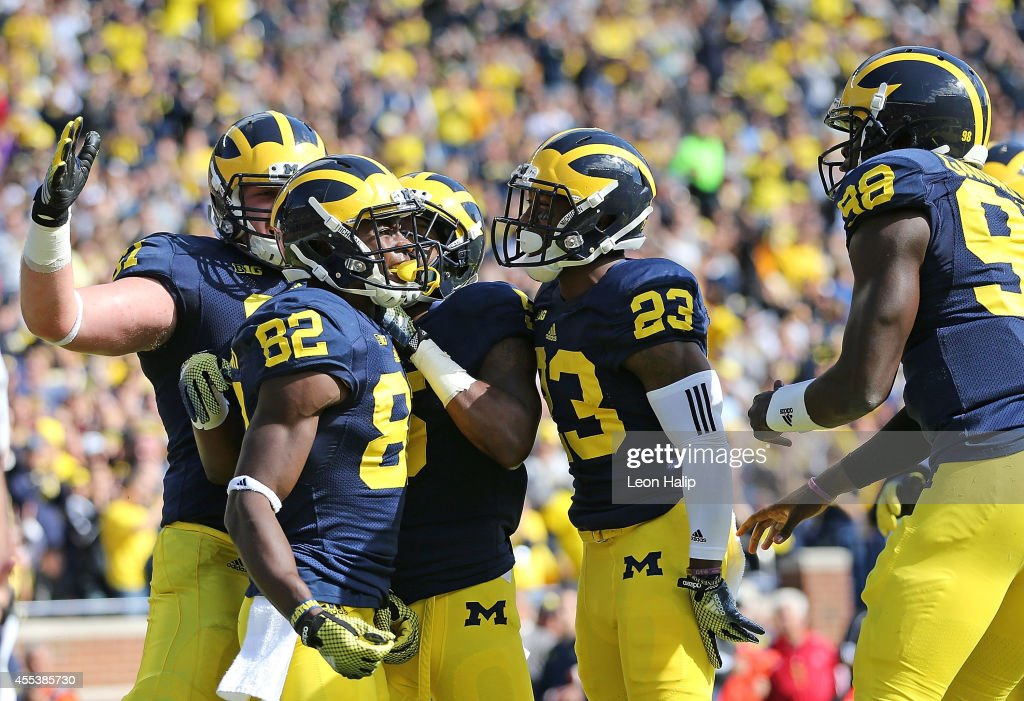 Amara Darboh of the Michigan Wolverines celebrates with his teammates after scoring on a 17yard pass from Devin Gardner during the first half of the...