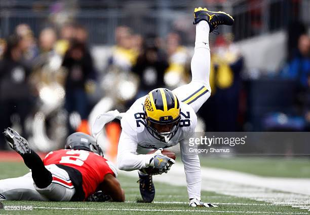 Amara Darboh of the Michigan Wolverines is tackled by Marshon Lattimore of the Ohio State Buckeyes after catching a pass during the first quarter of...