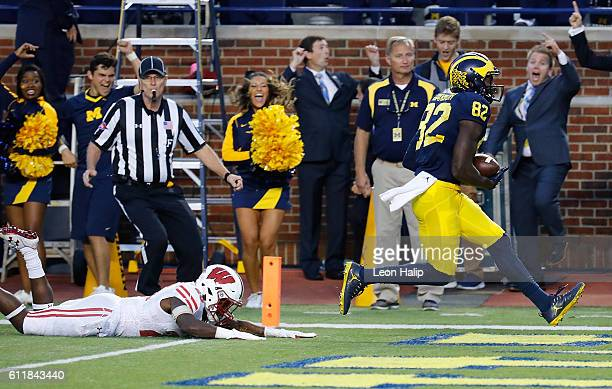 Amara Darboh of the Michigan Wolverines scores on a fourth quarter touchdown pass as Eric Burrell of the Wisconsin Badgers gives chase during the...