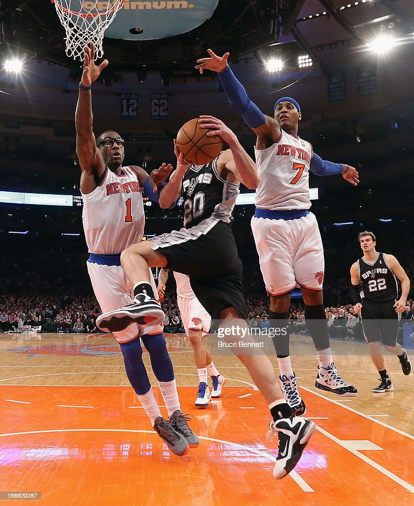 Amar'e Stoudemire #1 and Carmelo Anthony #7 of the New York Knicks combine to stop Manu Ginobili #20 of the San Antonio Spurs at Madison Square Garden on January 3, 2013 in New York City.