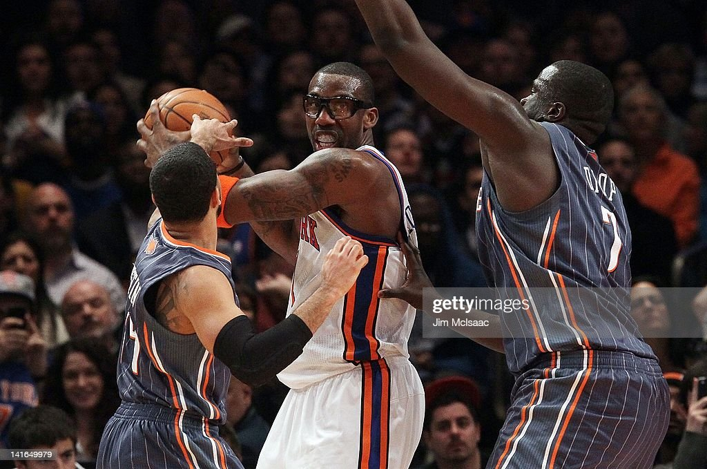 Amar'e Stoudemire #1 of the New York Knicks in action against D.J. Augustin #14 and DeSagana Diop #7 of the Charlotte Bobcats on January 9, 2012 at Madison Square Garden in New York City. The Knicks defeated the Bobcats 91-87.